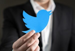 man holding Twitter bird logo