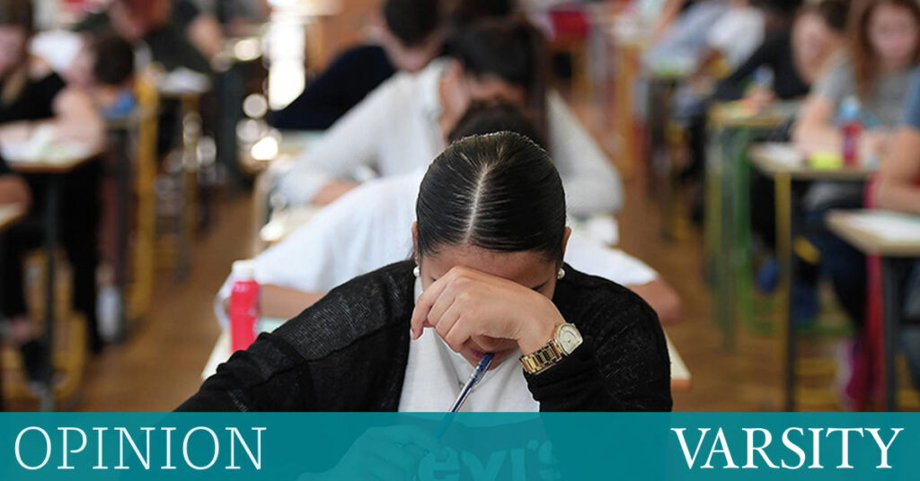Student with head down in an exam looking worried