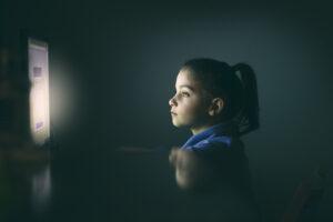 girl using computer at night