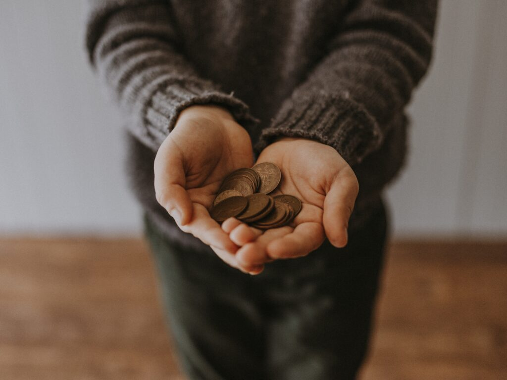 person holding out a handful of coins